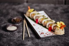 Les divers genres de sushi ont servi sur la pierre noire photos stock