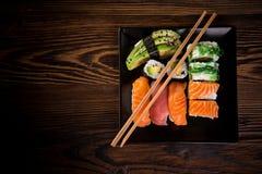 Les divers genres de sushi ont servi sur la table en bois Photos stock