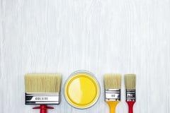 Les divers pinceaux et la peinture jaune peuvent sur le Ba gris en bois de bureau Images stock