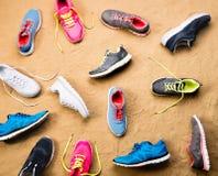 Les diverses chaussures de sports se sont étendues sur la plage de sable, tir de studio Photos stock