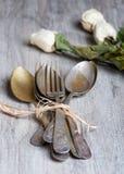Les diverses cuillères et fourchettes se sont enlacées sur la table en bois rustique Photos stock