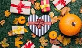 Les diverses feuilles d'automne et les potirons oranges s'approchent de la boîte de forme de coeur Image stock