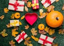 Les diverses feuilles d'automne et les potirons oranges s'approchent de la boîte de forme de coeur Photos libres de droits