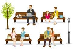 Les diverses personnes s'asseyent sur un banc Images stock