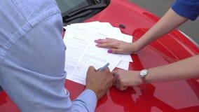 Les documents se trouvent sur la voiture de rouge d'af de capot Points de fille sur deux endroits pour le soupir Le type met là s banque de vidéos