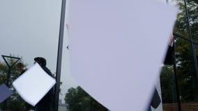 Les documents sur papier de lancement d'homme d'affaires dans l'air et célèbre le succès sur le fond d'immeuble de bureaux Libert banque de vidéos