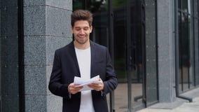 Les documents sur papier de lancement de jeune homme d'affaires dans l'air et célèbre le succès sur le fond moderne d'immeuble de banque de vidéos