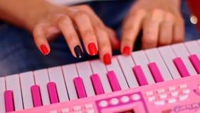Les doigts de femme de plan rapproché jouent le piano rose de clavier de jouet banque de vidéos
