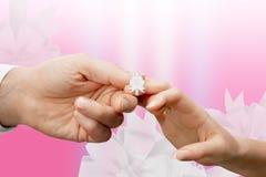 Les doigts de la femme et de l'homme attachés avec un ruban blanc Photographie stock libre de droits