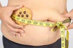 Les doigts de la femme mesurant sa graisse de ventre Photographie stock