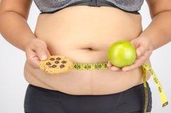 Les doigts de la femme mesurant sa graisse de ventre Photographie stock libre de droits