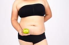 Les doigts de la femme mesurant sa graisse de ventre Image stock
