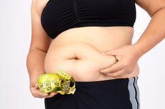 Les doigts de la femme mesurant sa graisse de ventre Photo stock