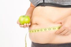 Les doigts de la femme mesurant sa graisse de ventre Photo libre de droits