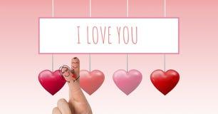 Les doigts de Valentine aiment les couples et je t'aime le texte et les coeurs pétillants de valentines accrochant sur la ficelle Image stock