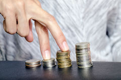Les doigts marchent sur des piles des pièces de monnaie, symbolisant la croissance et le progrès financiers dans les affaires Con image stock