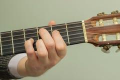 Les doigts sur les ficelles de jouer de guitare Photographie stock libre de droits