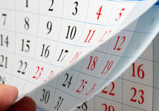 Les doigts tiennent la feuille de calendrier Photos libres de droits