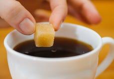 Les doigts tiennent un morceau de sucre de morceau au-dessus de tasse de thé Photos stock