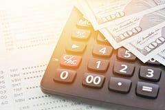 Les dollars américains encaissent l'argent, la calculatrice sur le carnet de compte d'épargne d'épargnes ou le relevé de compte f photographie stock libre de droits