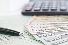 Les dollars américains encaissent l'argent, la calculatrice sur le carnet de compte d'épargne d'épargnes ou le relevé de compte f images stock