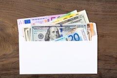 Les dollars et les euros dans le blanc enveloppent sur le fond en bois Photographie stock libre de droits