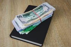 Les dollars am?ricains, euros, roubles sont sur un carnet noir Le concept d'un plan financier pour l'ann?e, l'investissement ou l photo libre de droits