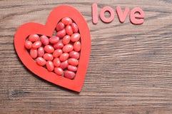 Les dragées à la gelée de sucre rouges montrées à un coeur rouge forment avec l'amour de mot Images stock