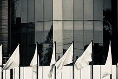 Les drapeaux blancs devant un bâtiment architectural moderne photographient photo stock