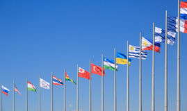 Les drapeaux de beaucoup de pays flottent sur le fond du ciel bleu dans le jour ensoleillé Image stock