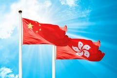 Les drapeaux de Hong Kong et de la Chine flottent dans la brise Image stock