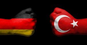 Les drapeaux de l'Allemagne et de la Turquie peintes sur deux ont serré le parement de poings Photos stock