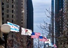 Les drapeaux des Etats-Unis, de l'Illinois et de Chicago volent un jour venteux le long de pont d'avenue du Michigan en hiver Photographie stock