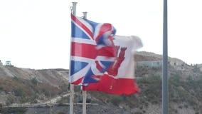 Les drapeaux du R-U et du Gibraltar banque de vidéos