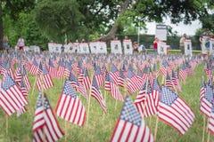 Les drapeaux am?ricains de pelouse avec la rang?e trouble des personnes portent les soldats tomb?s que les banni?res d?filent photos stock