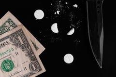 Les drogues et l'argent ont dispersé sur un fond noir images stock