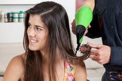 Les drys de coiffeur la femme heureuse des cheveux un image stock