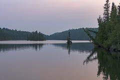 Les eaux calmes au crépuscule dans les bois du nord photo stock