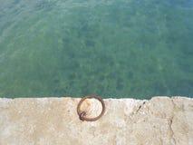 Les eaux de Teal et un fer sonnent dans un dock Image stock