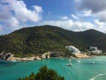 Les eaux et le pin de turquoise ont couvert des collines de la baie de Cala Llonga, Med photos stock