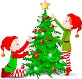 Les elfes décorent un arbre de Noël Images libres de droits