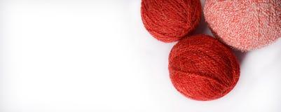 Les embrouillements de rouge et de rose du tricotage filète sur un fond blanc Image libre de droits