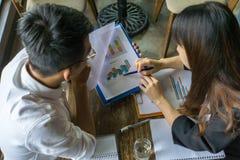 Les employés asiatiques discutent au sujet du rapport image stock