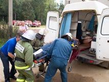Les employés d'EMERCOM chargent la victime dans une ambulance photographie stock libre de droits