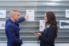 Les employés de bureau discutent les programmes qui accrochent sur le mur images stock