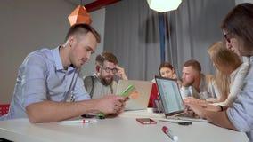 Les employés de bureau utilisent des ordinateurs portables et des comprimés lors de la réunion d'affaires clips vidéos