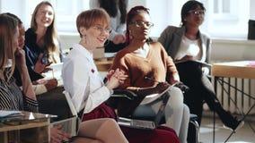 Les employés féminins multi-ethniques de sourire heureux de société commerciale discutent le travail lors du séminaire moderne de clips vidéos