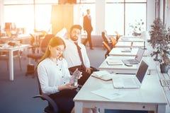 Les employés tournent au ralenti dans le bureau moderne ensoleillé photo stock