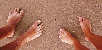 Les empreintes de pas couplent dans l'amour dans le sable sur la plage Image libre de droits