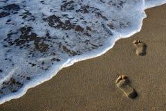 Les empreintes de pas dans le sable vont à la mer Image libre de droits